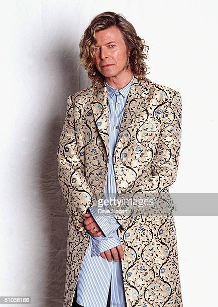 Musician David Bowie poses backstage at the Glastonbury festival in a coat designed by Alexander McQueen at Worthy Farm Pilton on June 25 2000 in...