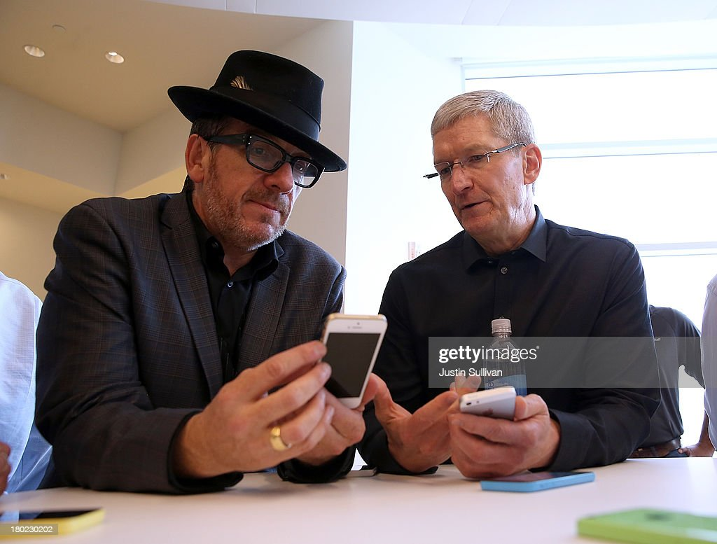 Musician Elvis Costello (L) and Apple CEO Tim Cook look at the new iPhone 5S during an Apple product announcement at the Apple campus on September 10, 2013 in Cupertino, California. The company launched the new iPhone 5C model that will run iOS 7 is made from hard-coated polycarbonate and comes in various colors and the iPhone 5S that features fingerprint recognition security.