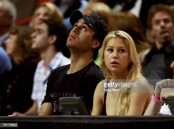 Musician Enrique Iglesias and former tennis player Anna Kournikova sit courtside as the Miami Heat take on the Cleveland Cavaliers at American...