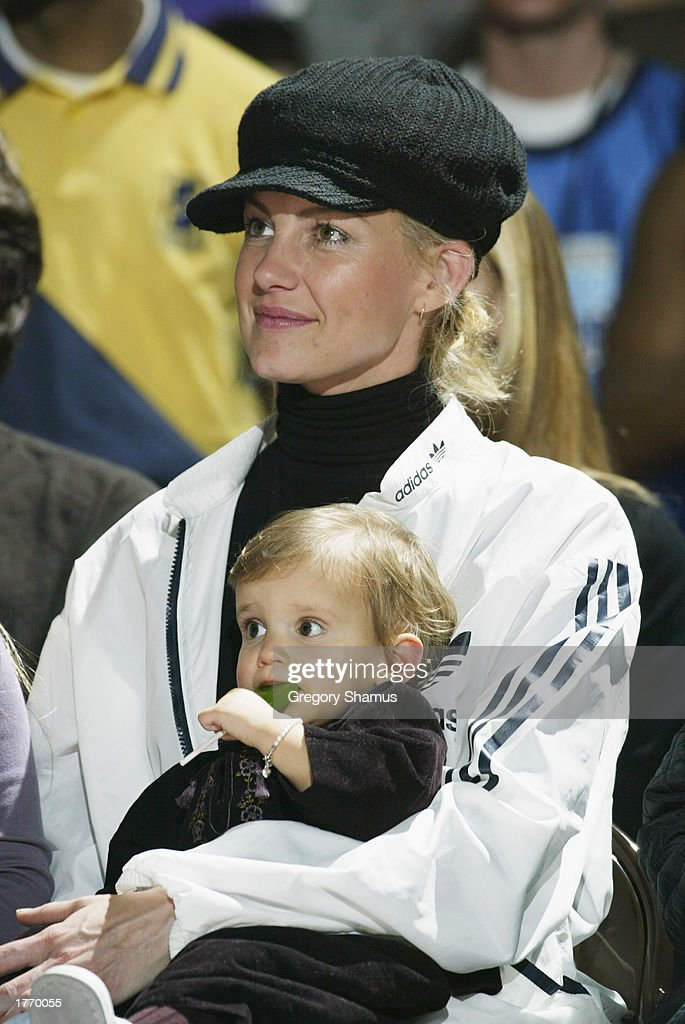Musician Faith Hill and her child watch the Celebrity Game at NBA Jam Session during the 2003 NBA All Star Weekend at the Georgia World Congress...
