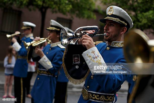 A musician from 'Santa Genoveva' brotherhood plays a trumpet with an image of Jesus Christ during a procession on April 14 2014 in Seville Spain...