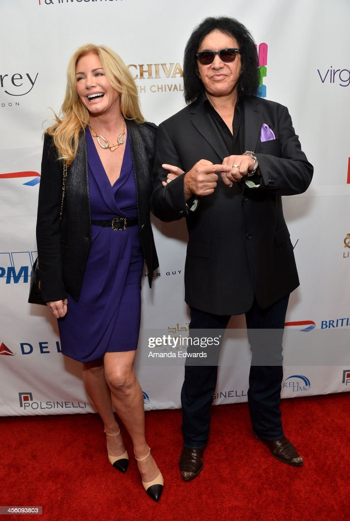 Musician Gene Simmons (R) and his wife Shannon Tweed-Simmons arrive at The British American Business Council Los Angeles 54th Annual Christmas Luncheon at the Fairmont Miramar Hotel on December 13, 2013 in Santa Monica, California.