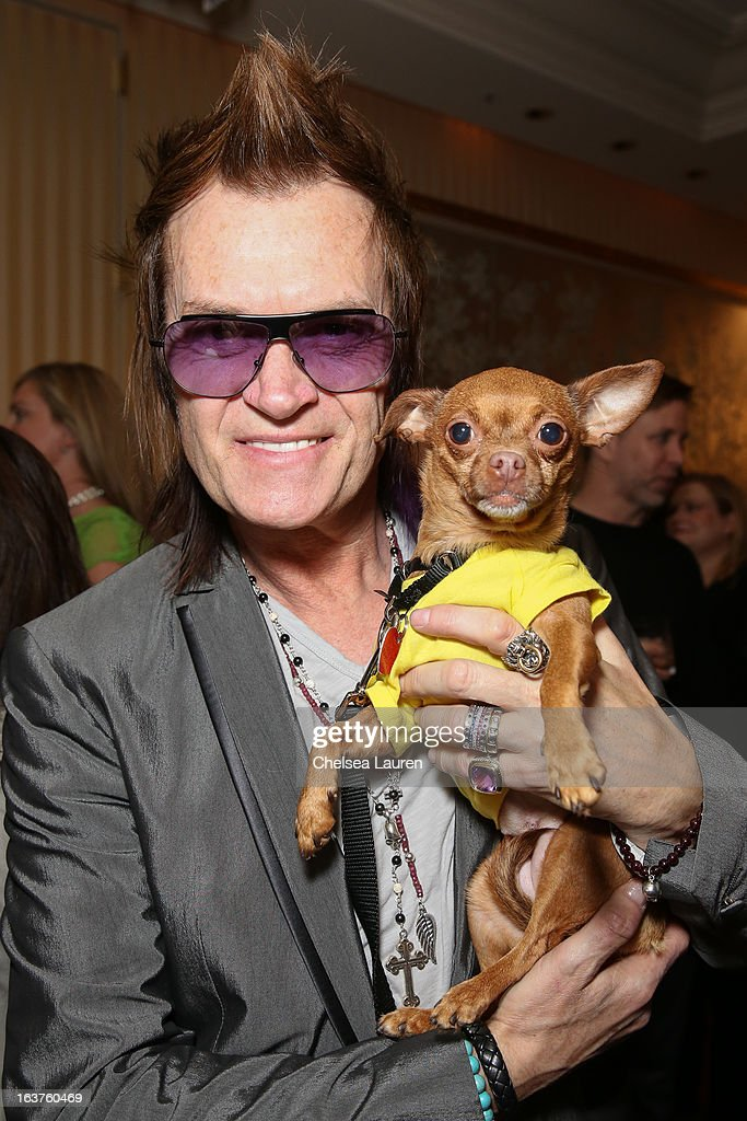 Musician Glenn Hughes poses with a dog wearing Lyric Culture for PetSmart at Much Love Animal Rescue's makeovers for mutts at Peninsula Hotel on March 14, 2013 in Beverly Hills, California.