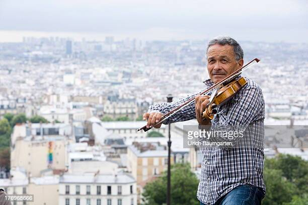 Musician in front of the Roman Catholic basilica SacreCoeur with view of the mass of houses of the French capital Paris on August 07 2013 in Paris...