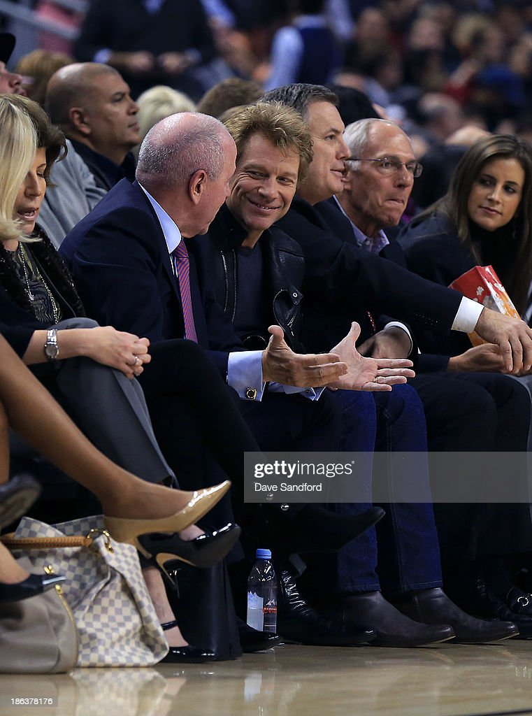 Musician John Bon Jovi shares a laugh with Chairman of Maple Leaf Sports & Entertainment <a gi-track='captionPersonalityLinkClicked' href=/galleries/search?phrase=Larry+Tanenbaum&family=editorial&specificpeople=695587 ng-click='$event.stopPropagation()'>Larry Tanenbaum</a> as they sit court side as the Boston Celtics face the Toronto Raptors during their NBA game at the Air Canada Centre on October 30, 2013 in Saint John, New Brunswick, Canada.