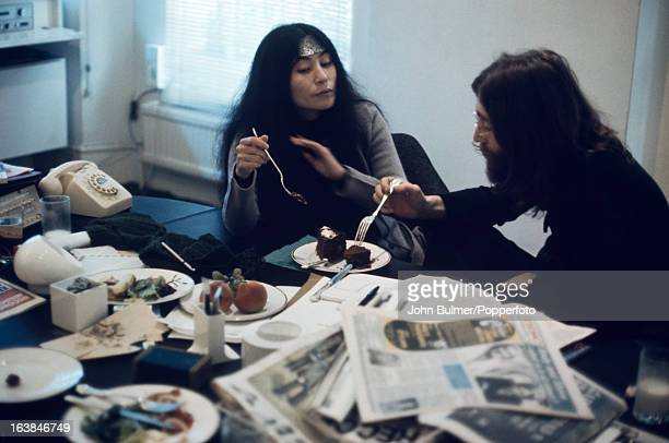 Musician John Lennon and his wife artist Yoko Ono share a cake at the Apple offices in London 1969