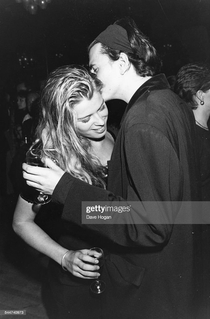 Musician John Taylor of the band 'Duran Duran' whispering in the ear of his girlfriend actress Amanda de Cadenet at a party circa 1990