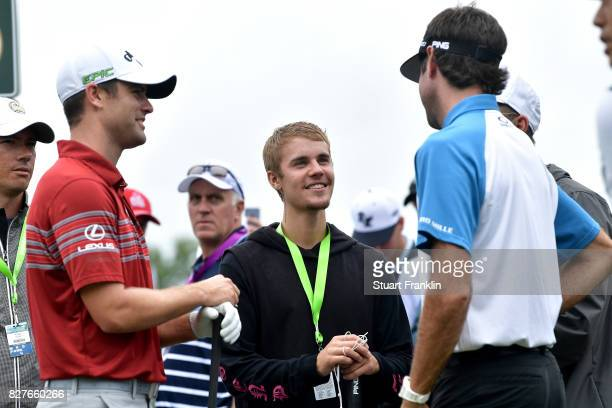 Musician Justin Bieber speaks to Wesley Bryan and Bubba Watson of the United States during a practice round prior to the 2017 PGA Championship at...