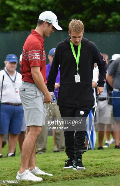 Musician Justin Bieber speaks to Wesley Bryan of the United States during a practice round prior to the 2017 PGA Championship at Quail Hollow Club on...