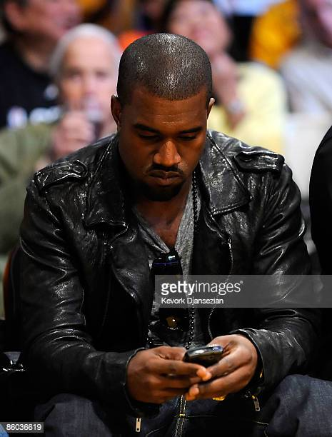 Musician Kanye West looks down at his cell phone from his courtside seat during the Los Angeles Lakers and Utah Jazz Game One of the Western...