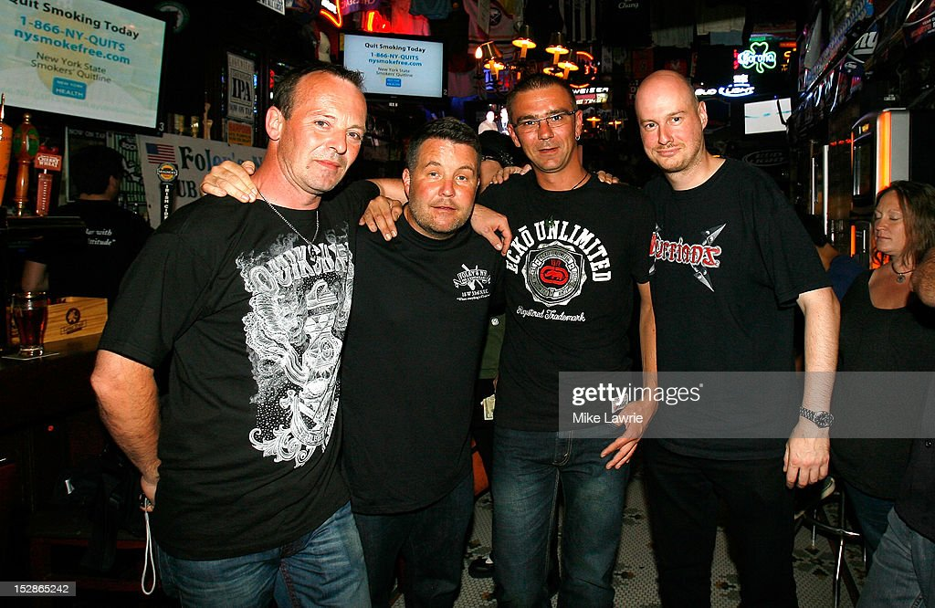 Musician Ken Casey (2nd L) of Dropkick Murphys poses with fans as he guest bartends as part of a Super Bowl XLVI wager at Foley's NY Pub on September 27, 2012 in New York City. Casey, who owns McGreevy's Bar in Boston, lost a Super Bowl bet to Foley's owner Shaun Clauncy.