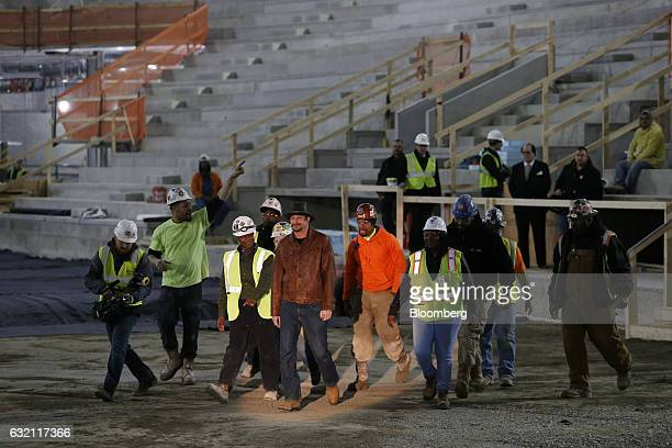 Musician Kid Rock center arrives with workers to a press conference at the Little Caesars Arena in Detroit Michigan at the Little Caesars Arena in...