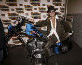 Musician Kid Rock sits on the AOL Top Speed motorcycle following a press conference for the halftime show for Super Bowl XXXVIII at the George R...