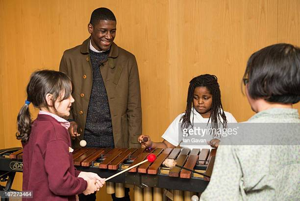Musician Labrinth listens to children playing a xylophone during his visit to the Nordoff Robbins music therapy centre on April 23 2013 in London...