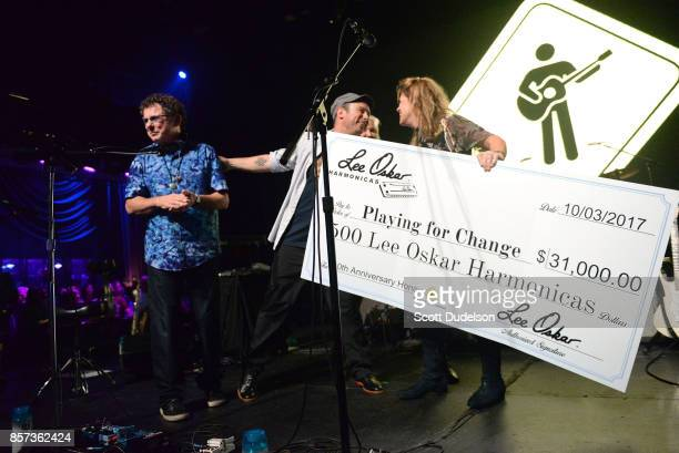 Musician Lee Oskar presents Playing for Change founder Mark Johnson a check during the We are One Benefit concert at The Mayan on October 3 2017 in...