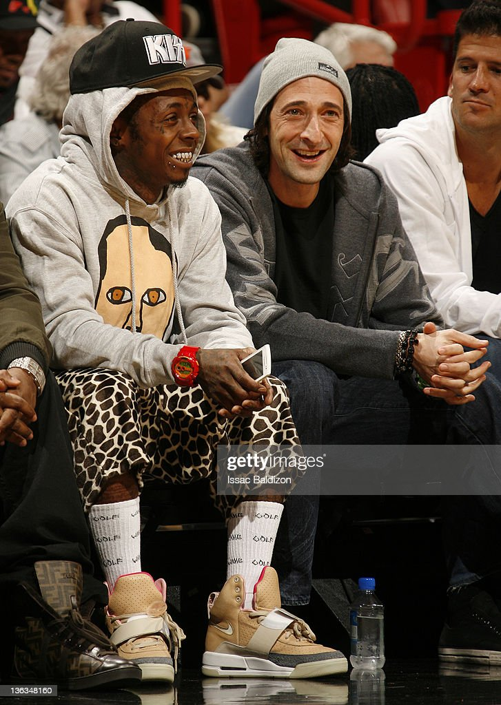 Musician Lil Wayne (left) and actor Adrien Brody (right) watch the game action between the Miami Heat and the Atlanta Hawks on January 2, 2012 at American Airlines Arena in Miami, Florida.
