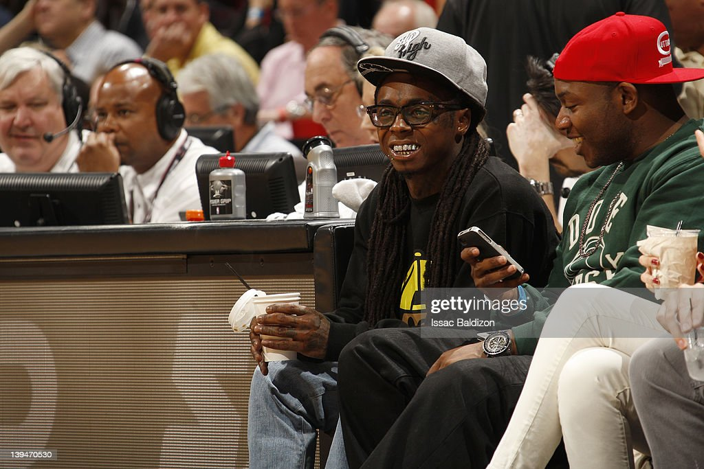 Musician Lil Wayne (left) watches the game between the Sacramento Kings and Miami Heat on February 21, 2012 at American Airlines Arena in Miami, Florida.