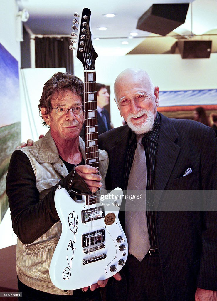 Musician Lou Reed holds up a signed guitar as he poses with actor Dominic Chianese at the 6th Annual Ten O'Clock Classics benefit gala at the The Union Square Ballroom on November 10, 2009 in New York City.