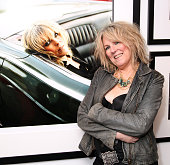 Musician Lucinda Williams poses next to a portrait of herself at the Danny Clinch exhibition opening at Morrison Hotel Gallery on October 23 2014 in...