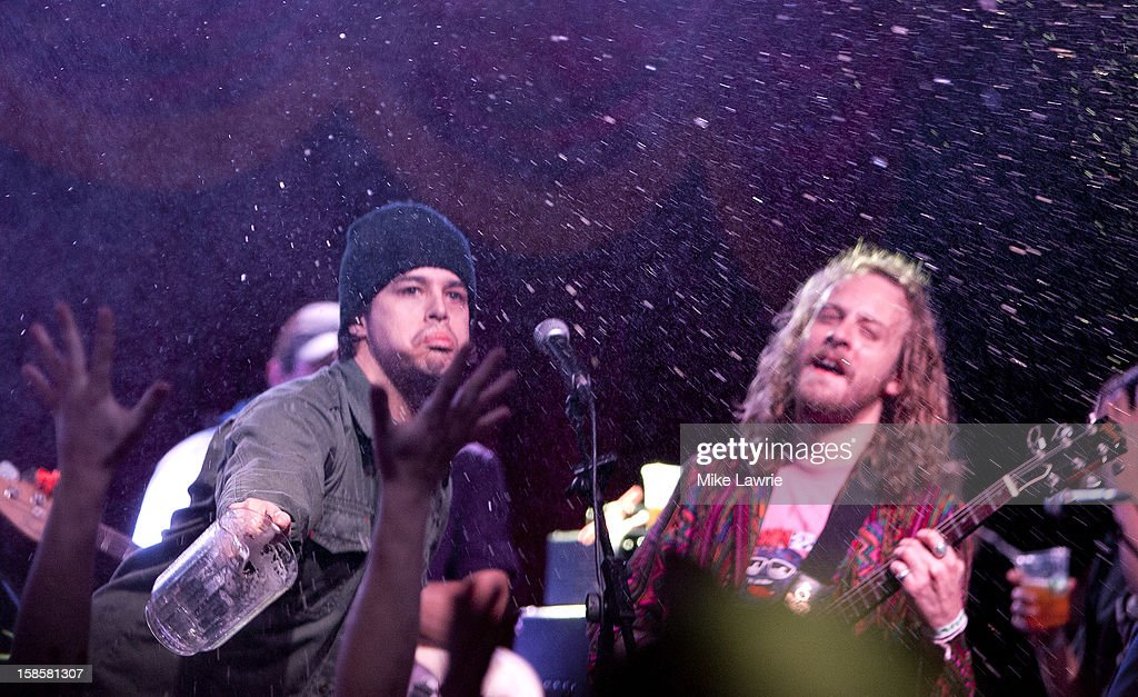 Musician Matt Vasquez (L) of Delta Spirit throws a pitcher of beer at the crowd as he performs with John McCauley of Deer Tick at Brooklyn Bowl on December 19, 2012 in New York City.