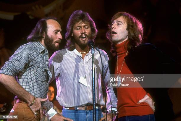 Musician Maurice Barry and Robin Gibb of the Bee Gees singing on stage