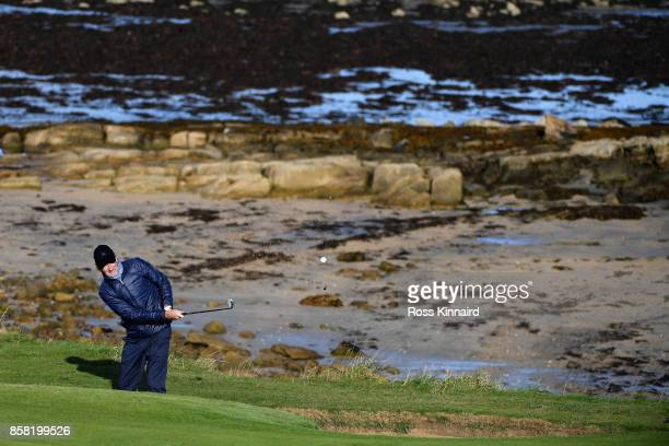Musician Mike Rutherford chips onto the 12th green during day two of the 2017 Alfred Dunhill Championship at Kingsbarns on October 6 2017 in St...