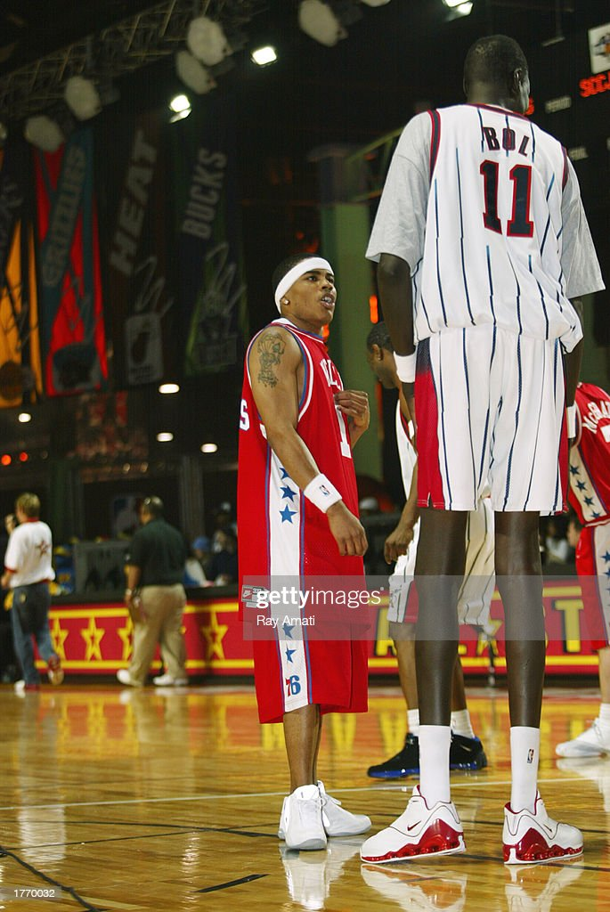 Musician Nelly talks to former NBA star Manute Bol during the Celebrity Game at the NBA Jam Session at the Georgia World Congress Center on February...