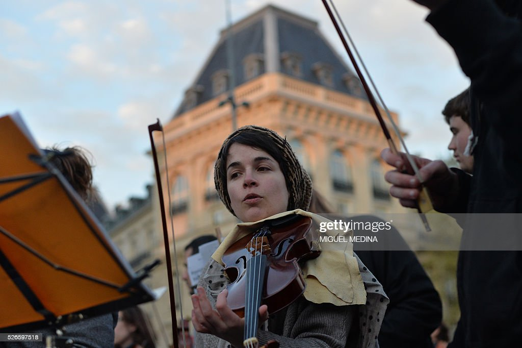 A musician of the orchestra of classical music 'Standing Musicians' rehearses prior a concert at the Place de la Republique in Paris during the 'Nuit Debout' (Up All Night) movement against the French government's proposed labour reforms on April 30, 2016. / AFP / MIGUEL