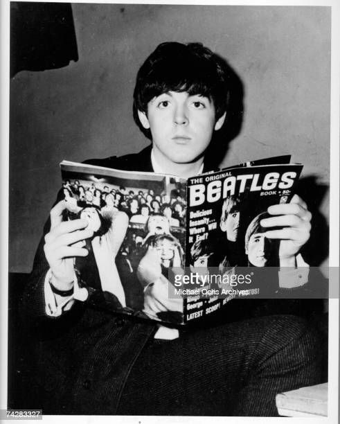 Musician Paul McCartney of the rock and roll band 'The Beatles' poses for a portrait holding a Beatles fanzine which depicts 'Beatlemania' on the...