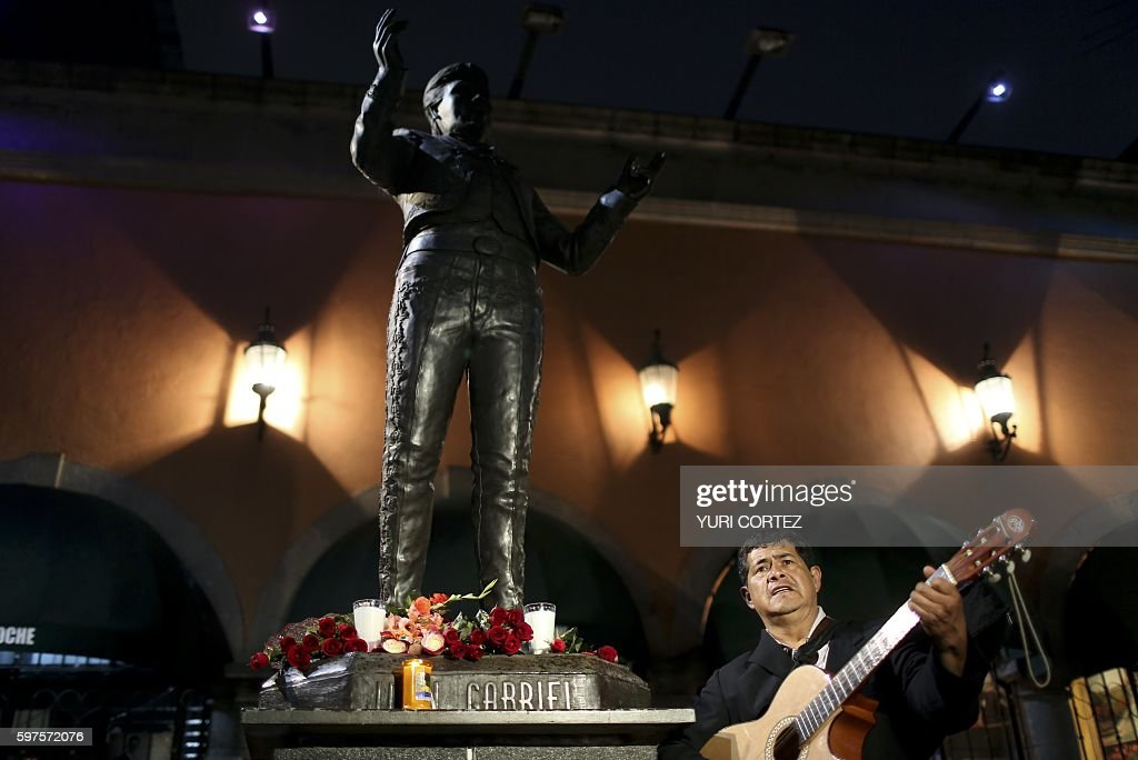 A musician performs a song before the statue of Mexican singer and composer 'Juan Gabriel' at the Plaza Garibaldi on August 28 2016 in Mexico City...