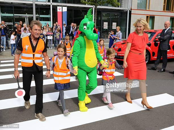 Musician Peter Maffay German Politician Manuela Schwesig and the Tabaluga dragon demonstrate road crossing safety to kids on September 8 2015 in...