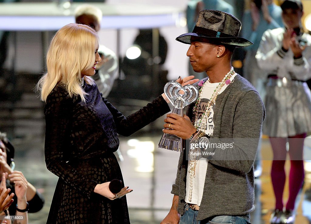 Musician Pharrell Williams (R) accepts the iHeartRadio Innovator Award from singer Gwen Stefani (L) onstage during the 2014 iHeartRadio Music Awards held at The Shrine Auditorium on May 1, 2014 in Los Angeles, California. iHeartRadio Music Awards are being broadcast live on NBC.