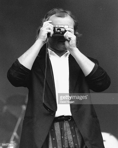 Musician Phil Collins taking a photograph at a concert July 6th 1987