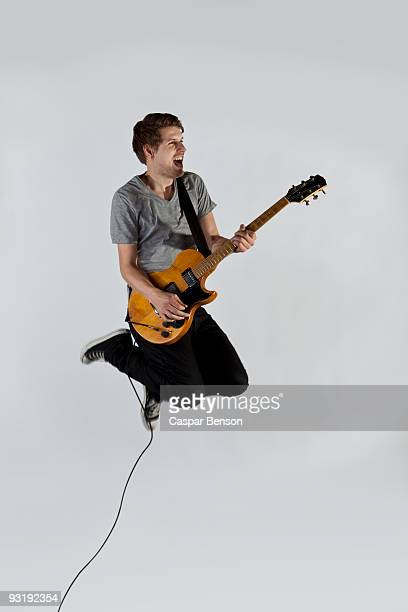A musician playing a guitar and jumping in mid-air