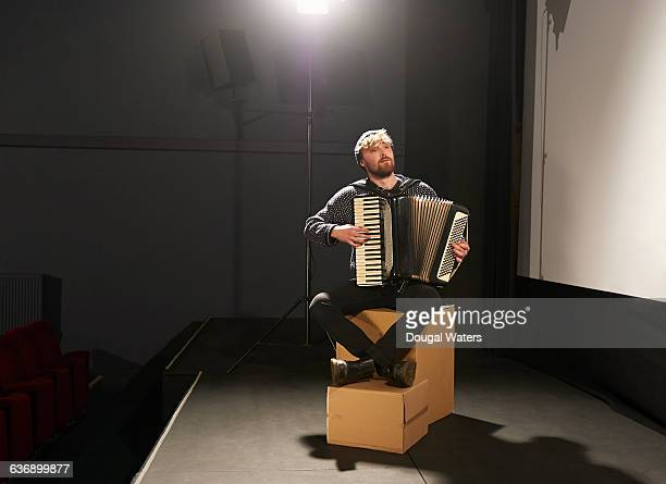 Musician playing accordion on small stage.