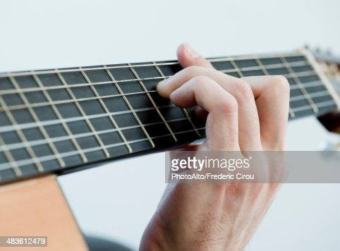 Musician playing acoustic guitar, close-up