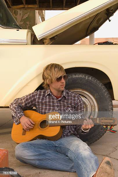 Musician playing acoustic guitar outdoors against truck