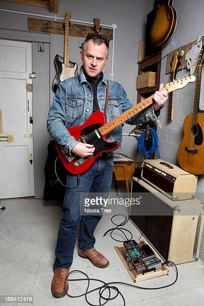 A musician playing guitars in his studio