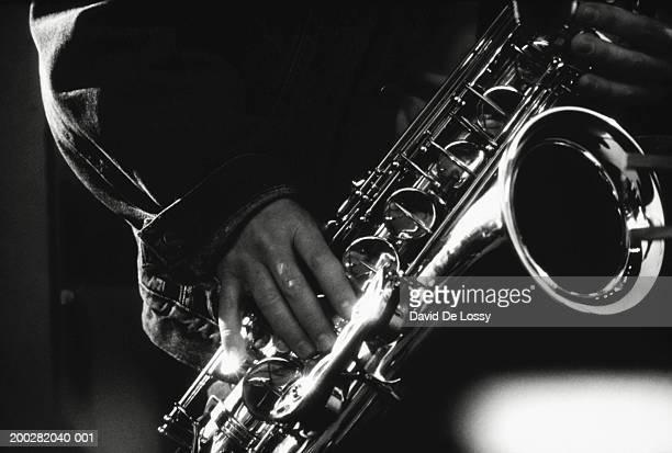 Musician playing saxophone, close-up, (B&W)