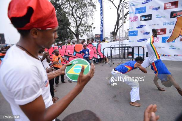 A musician plays a drum as men take part in an event dedicated to the practice of 'capoeira' an AfroBrazilian martial art in Kinshasa in the...