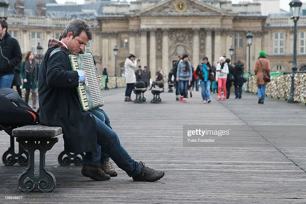 A musician plays an acordian on the Pont des Arts on January 4, 2013 in Paris, France. The nine-arch metallic footbridge completed in 1804 is one of the most romantic places of the capital where people visit it to attach love padlocks illustrated with their initials or messages of love, before throwing the key into the River Seine. The bridge is also a meeting place for artists who find inspiration from the surrounding views of the city.