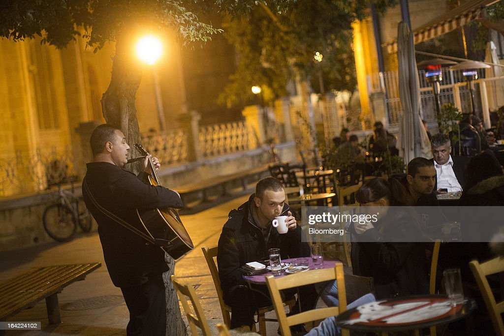 A musician plays his guitar for customers sitting in an outdoor restaurant during the evening in the old town of Nicosia, Cyprus, on Wednesday, March 20, 2013. European policy makers weighed how far to push Cyprus after lawmakers in the Mediterranean nation rejected an unprecedented levy on bank deposits, throwing into limbo a rescue package designed to keep it in the euro. Photographer: Simon Dawson/Bloomberg via Getty Images