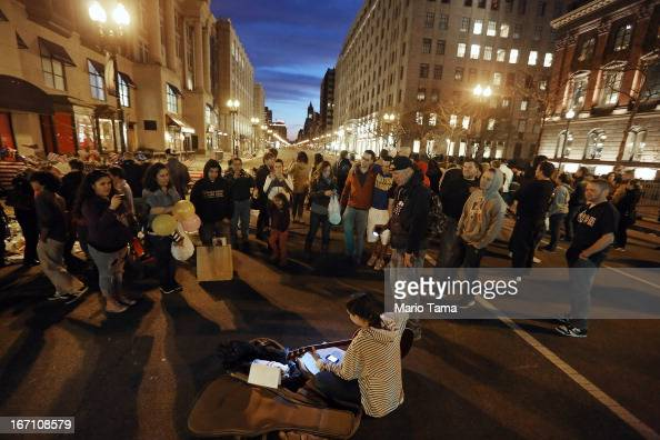 A musician plays patriotic tunes by a makeshift memorial for victims near the site of the Boston Marathon bombings at the edge of the stillclosed...