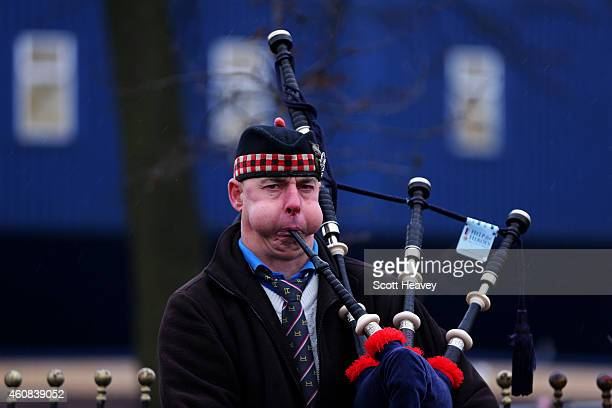 A musician plays the bagpipes outside the stadium before the Barclays Premier League match between West Bromwich Albion and Manchester City at The...