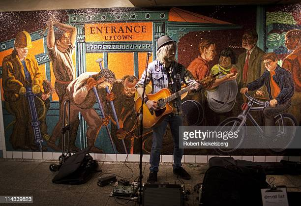 A musician plays the guitar at the Times Square 42nd Street subway station March 30 2011 in New York