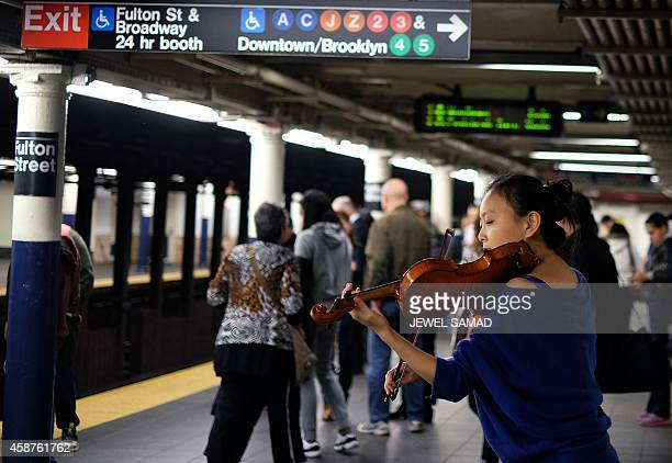A musician plays violin as commuters wait to catch their train at the Fulton Center subway station in New York on November 10 2014 The Fulton Center...