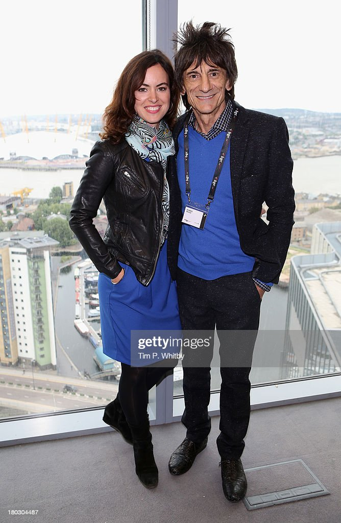 Musician Ronnie Wood and wife Sally Humphreys pose on the trading floor during the BGC Charity Day 2013 at BGC Partners on September 11, 2013 in London, England.