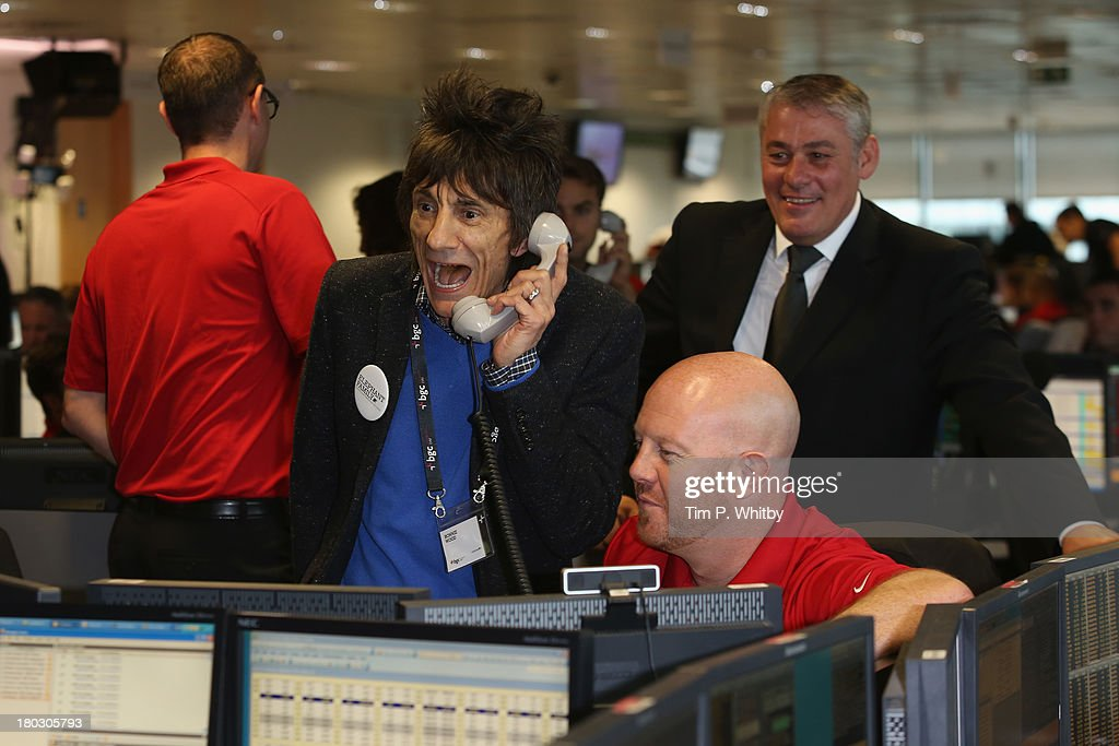 Musician Ronnie Wood speaks on the phone on the trading floor during the BGC Charity Day 2013 at BGC Partners on September 11, 2013 in London, England.