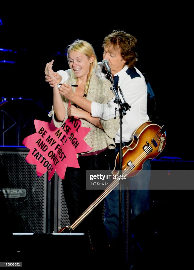 Musician Sir Paul McCartney signs a girls wrist who was holding a sign 'Paul Please Sign Me! BeMy First and Only Tattoo!' during his performance at the Lands End Stage during day 1 of the 2013 Outside Lands Music and Arts Festival at Golden Gate Park on August 9, 2013 in San Francisco, California.