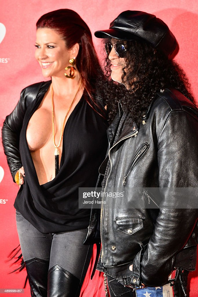 Musician Slash (R) and Perla Hudson arrive at the 2014 MusiCares MAP Fund Benefit Concert at Club Nokia on May 12, 2014 in Los Angeles, California.
